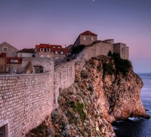 Walled town on a sea coast cliff HD wallpaper