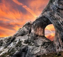 Sunset behind a portal in rocky cliff HD wallpaper