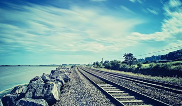 Water ocean rocks railroad tracks skies HD wallpaper