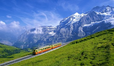 Train going up a gorgeous alpine landscape HD wallpaper