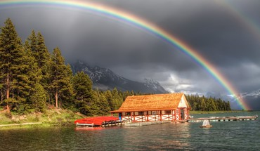 Rainbow over a boat house on river HD wallpaper