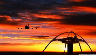 Airplane landing in front of a sunset HD wallpaper