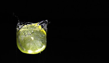 Lemon drop black background water HD wallpaper
