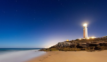 Bright lighthouse at night HD wallpaper