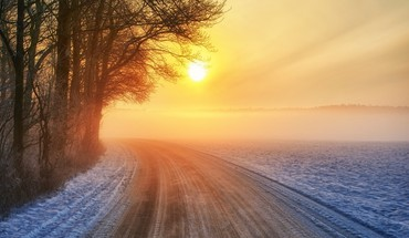Sunrise on a wintry countryside road HD wallpaper