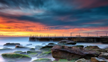 Wharf on a rocky shore at sunset HD wallpaper