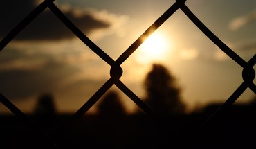 Blurred background chain link fence fences silhouettes sunset HD wallpaper