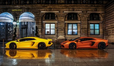 Two lamborghinis parked in front of the ritz HD wallpaper