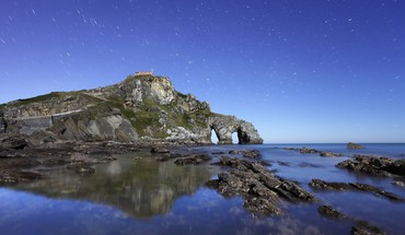 Star showers above a rocky sea coast HD wallpaper