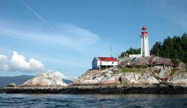 Wonderful lighthouse on rocky shore HD wallpaper
