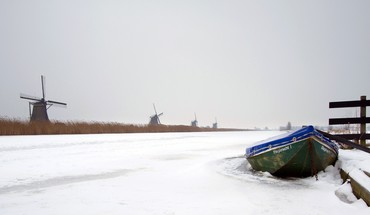 Row of windmills along a wintry channel HD wallpaper