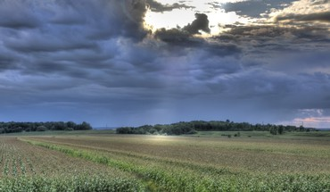 Sunrays through storm clouds over fields HD wallpaper