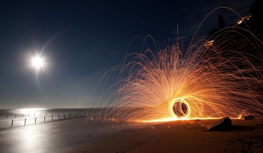 Circular sparkler on a beach at night HD wallpaper