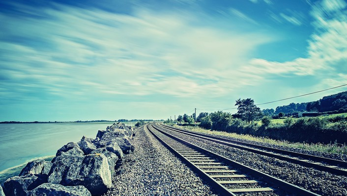 Water ocean rocks railroad tracks skies wallpaper