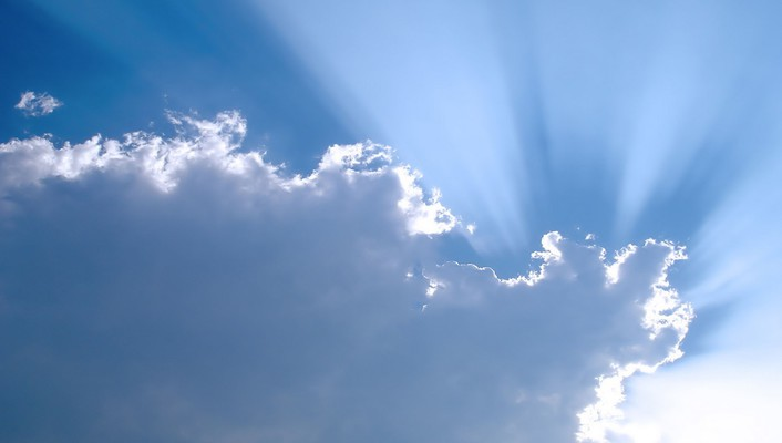The sun is peacking out of clouds wallpaper