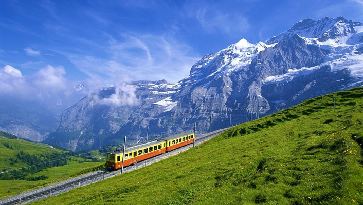 Train going up a gorgeous alpine landscape wallpaper