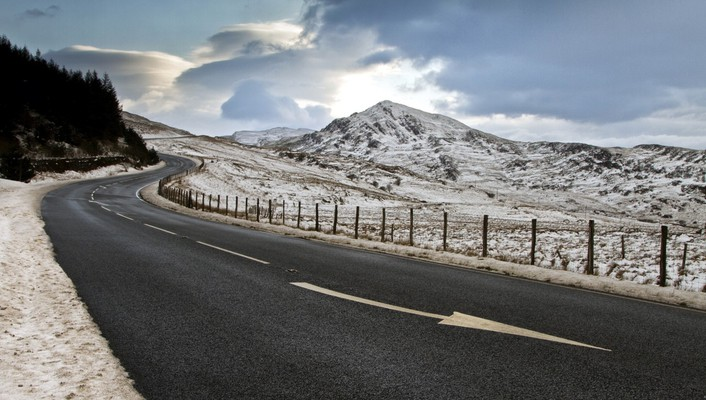 Blacktop highway coming down a mountain in winter wallpaper