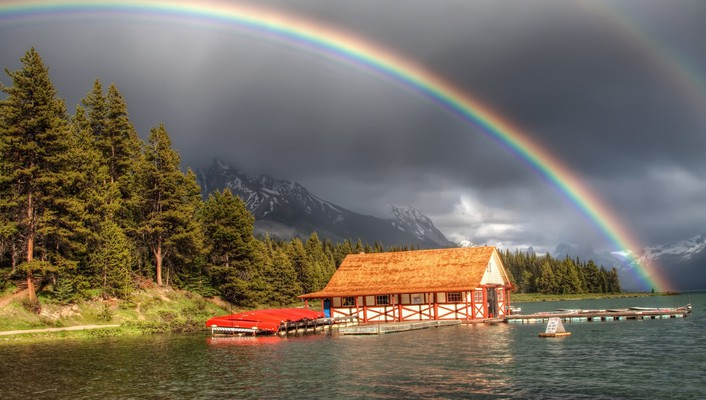 Rainbow over a boat house on river wallpaper