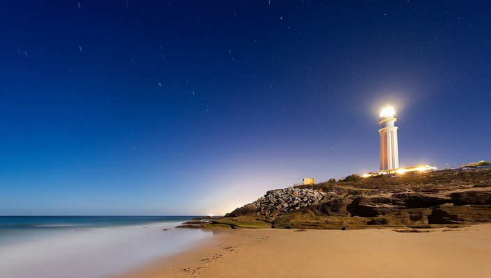 Bright lighthouse at night wallpaper