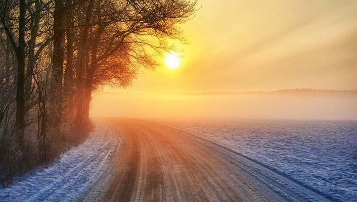 Sunrise on a wintry countryside road wallpaper