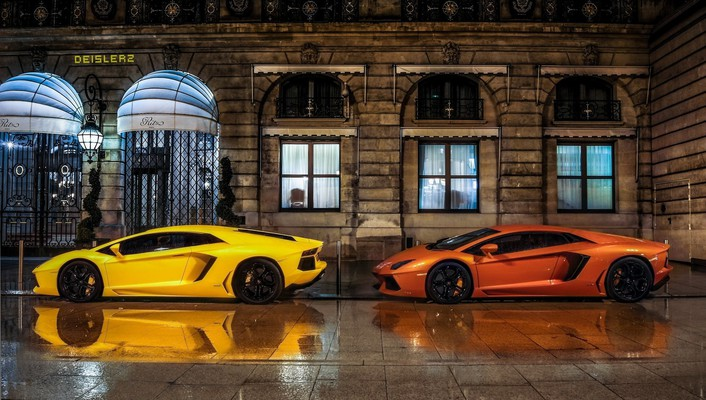 Two lamborghinis parked in front of the ritz wallpaper