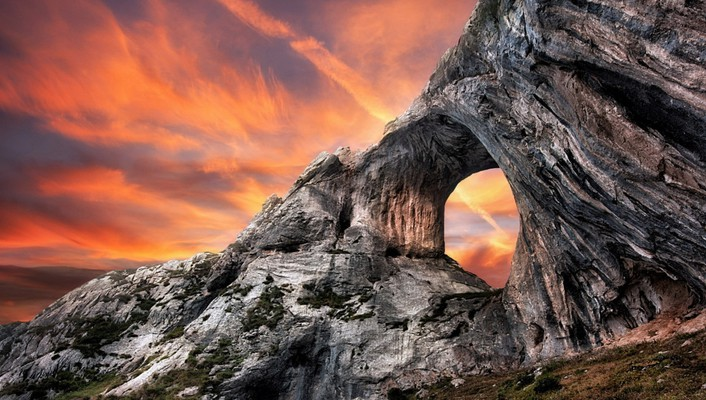 Sunset behind a portal in rocky cliff wallpaper