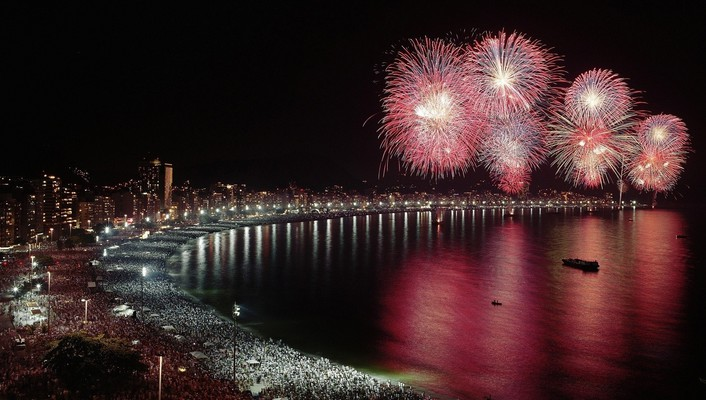 Fireworks over crowded city beach wallpaper