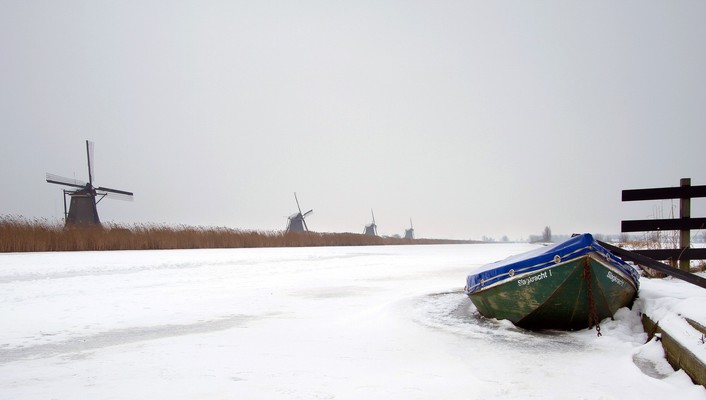 Row of windmills along a wintry channel wallpaper