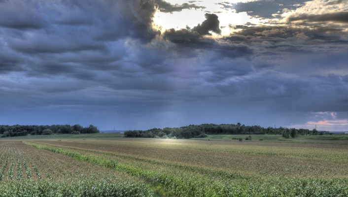 Sunrays through storm clouds over fields wallpaper