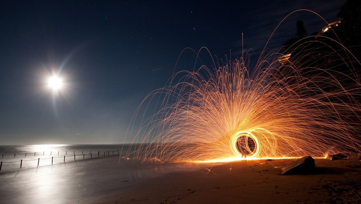 Circular sparkler on a beach at night wallpaper
