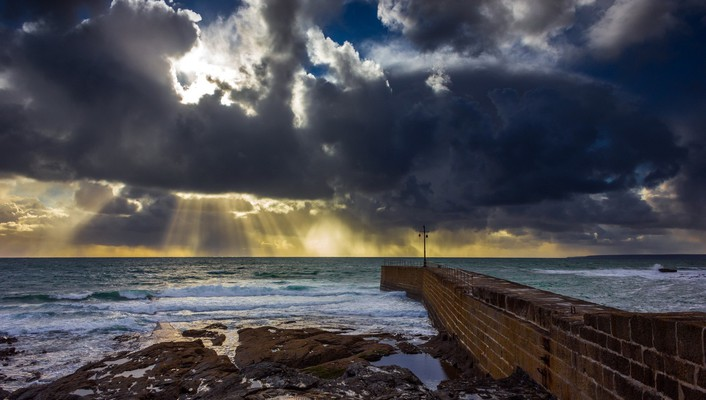 Pier into a sea under sun rays wallpaper